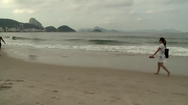 vídeos de stock e filmes b-roll de men in trunks passing woman on copacabana beach, with view of sugar loaf mountain [pã£o de aã§ãºcar], rio de janeiro, brazil [brasil] - copacabana