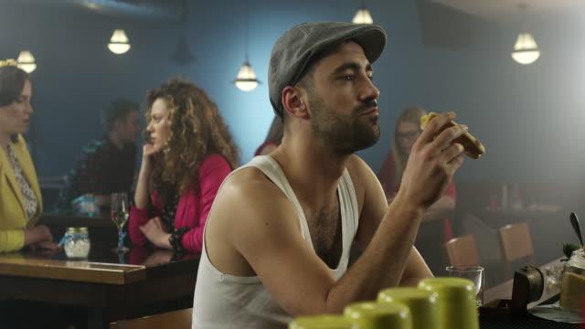 Hombres en camiseta, sentado y comer en el bar de cócteles