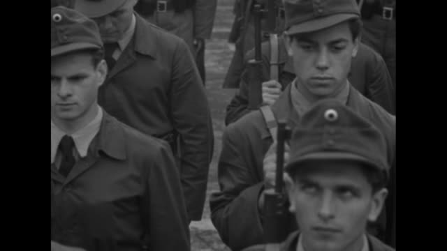 men in uniform carrying rifles march in unison forwards then break and form lines while carrying rifles horizontally and breaking into run / vs the... - 1951 stock-videos und b-roll-filmmaterial