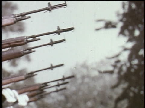 1965 montage men in uniform fire guns in military salute as fellow soldier begins to play bugle - 金管楽器点の映像素材/bロール
