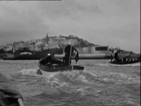 2 men in uniform in boat with a nazi flag drive away another boat with 10 people light house and small island in back - hakenkreuz stock-videos und b-roll-filmmaterial