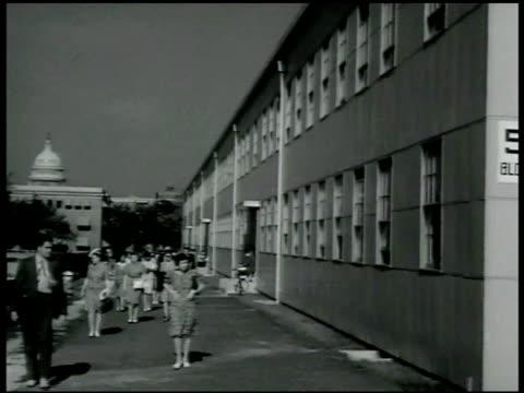 vidéos et rushes de men in uniform walking into war department building ext people walking along side out of temporary office building ws temporary office building in... - 1942