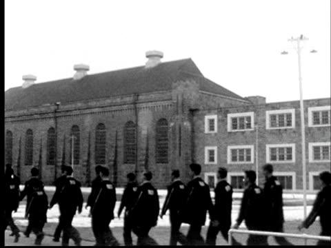1956 ws pan men in uniforms marching into old prison building through snow-covered courtyard at kansas state penitentiary/ lansing, kansas - prisoner walking stock videos & royalty-free footage