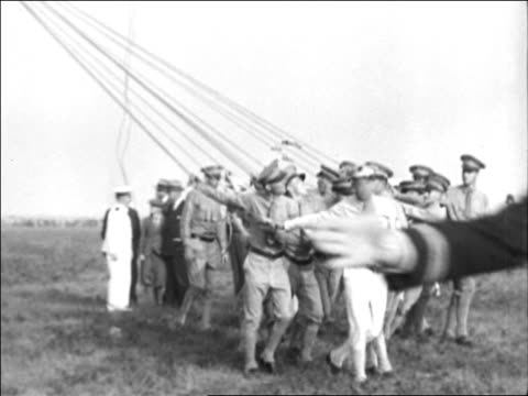 vídeos y material grabado en eventos de stock de men in uniforms pulling ropes attached to graf zeppelin / documentary - 1928