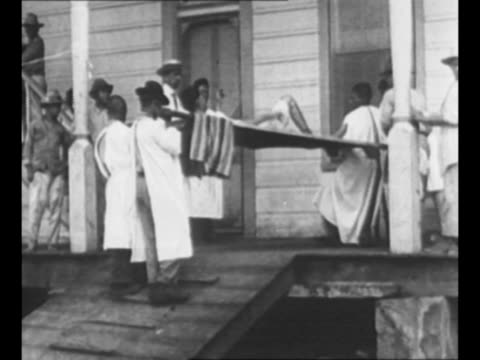 vídeos de stock, filmes e b-roll de men in white gowns carry man on stretcher up steps of nicaragua building set him onto a table on porch child on porch scurries away men walk away... - paramount building