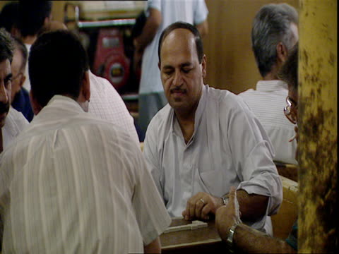 vídeos y material grabado en eventos de stock de men in white shirts in coffee shop playing backgammon / baghdad, iraq - only mature men