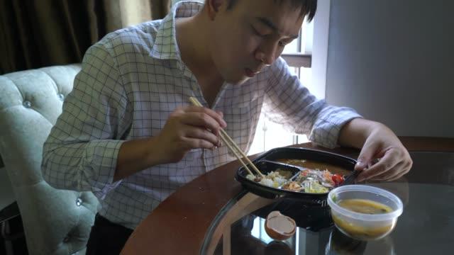 オフィスの仕事の日に昼休みに日本食を食べる仕事服の男性。 - unhealthy eating点の映像素材/bロール