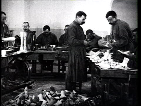 stockvideo's en b-roll-footage met 1915 b/w ws men in workshop making prostheses for war victims/ russia - 1915