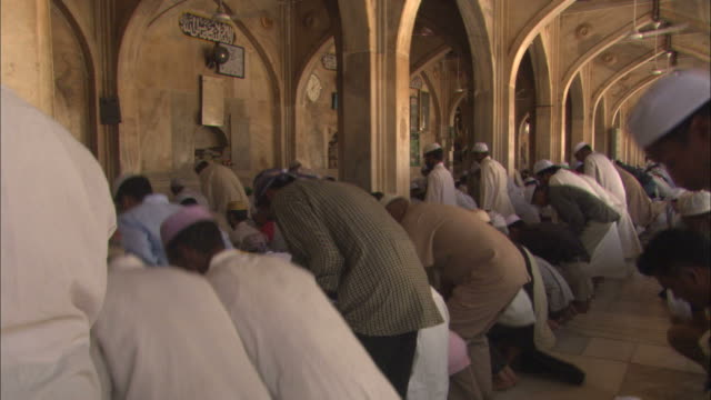 men inside a mosque bow and then kneel. - praying stock videos & royalty-free footage