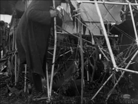 b/w 1925 men inspecting admiral byrd's airplane wreckage after transatlantic flight / france / docu - 1927年点の映像素材/bロール