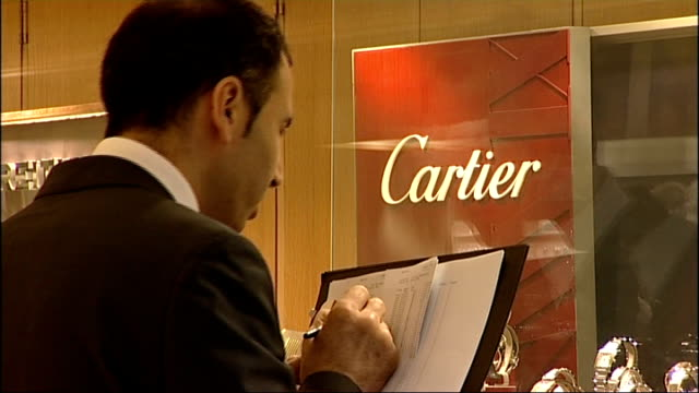 Men jailed for smash and grab raid in Kensington Man making notes as looking at Cartier and Rolex watches in jewellers window Close shot man with...