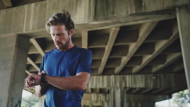 vídeos y material grabado en eventos de stock de hombres corriendo mirando smartwatch - varón