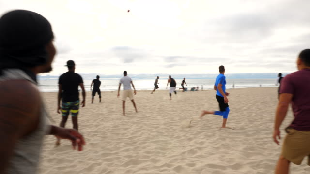 ts men jumping in celebration of touchdown during beach football game with friends - touch football video stock e b–roll