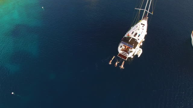 aerial men jumping into the sea off a sailboat - yacht stock videos & royalty-free footage
