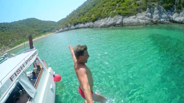 slo mo pov men jumping into the sea - nautical vessel stock videos & royalty-free footage