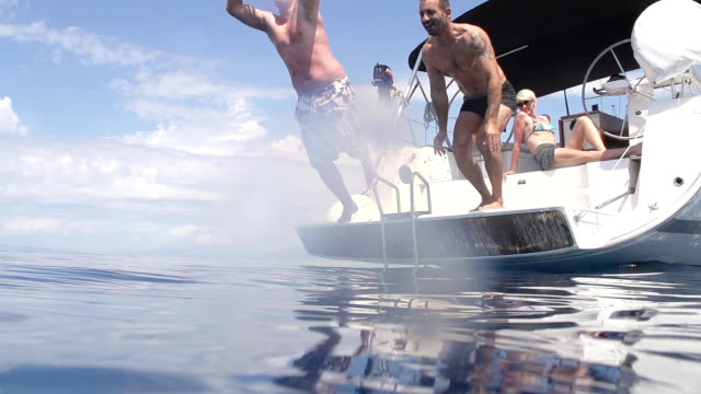 slo mo men jumping into the sea - yacht stock videos & royalty-free footage