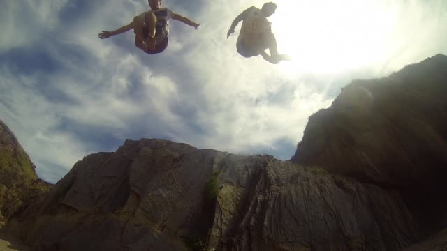 vídeos de stock e filmes b-roll de 2 men jumping off a cliff towards camera - rocha