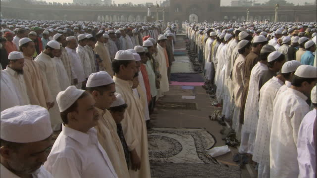 MS Men kneel and bow touching their faces to ground in prayer /Delhi, National Territory of Delhi, India