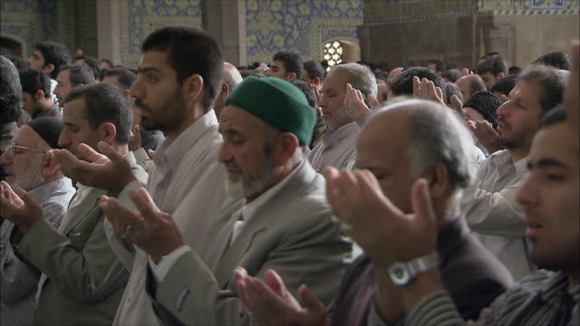 MS ZI Men kneeling during Friday prayers in Imam Mosque, Esfahan, Iran