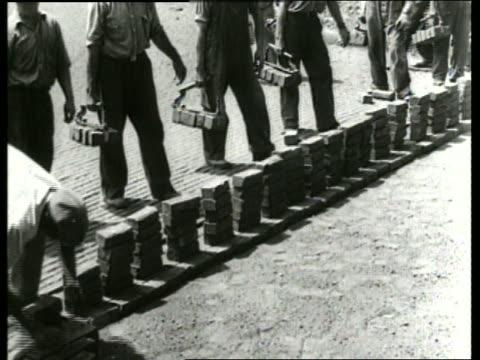 B/W men laying bricks on ground / SOUND