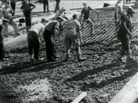 B/W 1934 men laying metal grid on hillside in WPA construction project / documentary