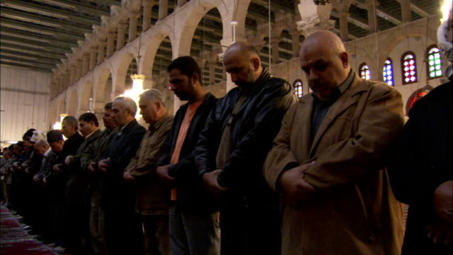 Men line up in a row to pray at the Umayyad Mosque Damascus. Available in HD.