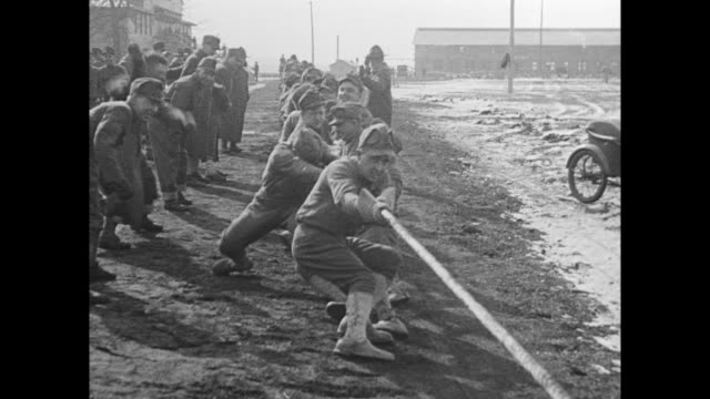 Men line up in civilian clothes to sign up for the military / men gathering around large medicine ball in tug of war contest / CU soldiers writing...
