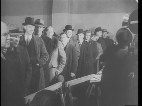 Men lined up and signing up for selective service / Japanese and Chinese men sit next to each other signing up / congressman and senator signing up /...
