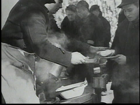 men lining up for a meal in the snow / hot food being served outdoors / workers sitting on logs to eat / workers rinsing out mugs - 1934 個影片檔及 b 捲影像