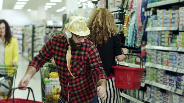 Männer, die Musik über Kopfhörer hören und tanzen im Supermarkt