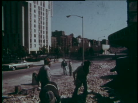 men load bricks on truck to clear the rubble of demolished tenement building, contrast with new high rise across the street. - construction worker stock videos & royalty-free footage