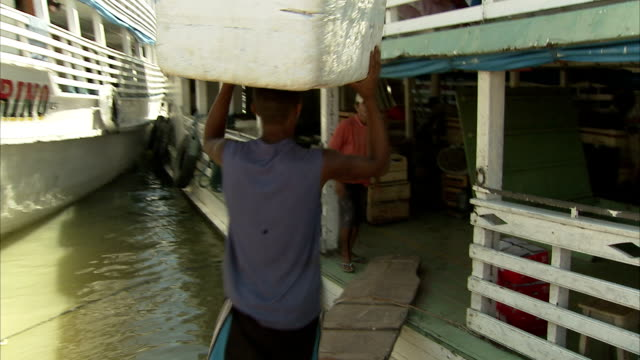 men load large boxes onto a ferry in brazil. available in hd. - ferry stock videos & royalty-free footage