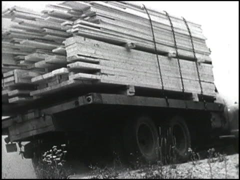 men load lumber onto a 1950 chevy truck the truck drives up a steep access road and climbs an even steeper winding road in the rocky mountains... - chevrolet truck stock videos & royalty-free footage