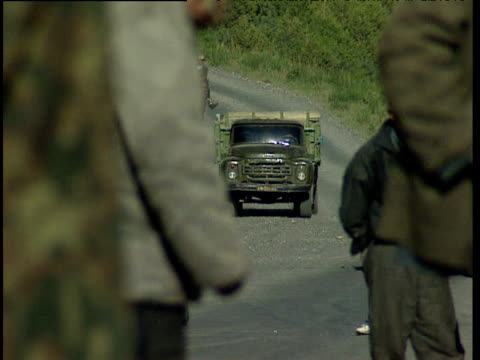 men loiter as truck joins stationary queue on rural road tajikistan - ムラがある点の映像素材/bロール