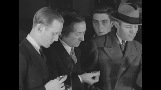 Men look at pocket watches then disperse during the time of Bruno Hauptmann's execution for the murder of the Lindbergh baby
