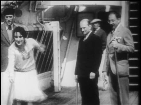 b/w 1928 men look on as woman shuffles in shuffleboard game on deck of ocean liner / newsreel - 1928 stock videos & royalty-free footage