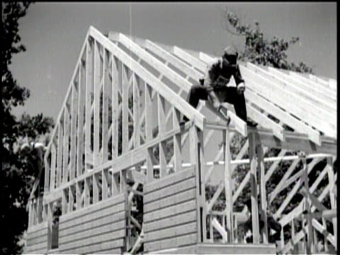 vidéos et rushes de men look over plans at a construction site / a man hammers at the frame of a roof / exterior of a large housing building / children play near the... - bidonville