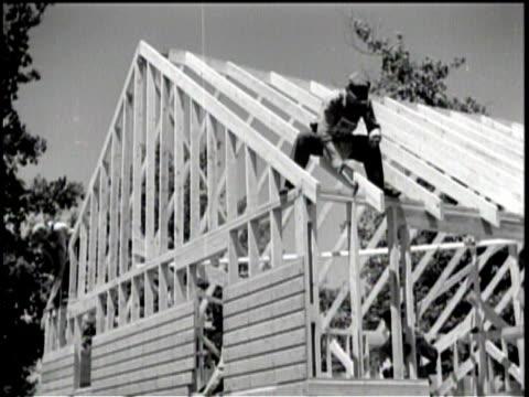 vidéos et rushes de men look over plans at a construction site / a man hammers at the frame of a roof / exterior of a large housing building / children play near the... - la grande dépression