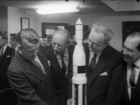 vídeos de stock e filmes b-roll de b/w 1958 3 men looking at model rocket / 1 is werner von braun / newsreel - 1958