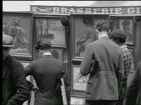 B/W 1927 REAR VIEW men looking at paintings in sidewalk art show / Paris, France