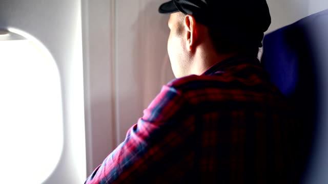männer suchen durch flugzeug fenster und schließen des fensters - sitz stock-videos und b-roll-filmmaterial