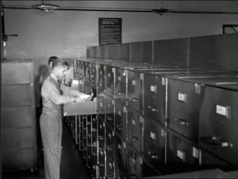 B/W 1937 men looking thru row of filing cabinets / Buick factory