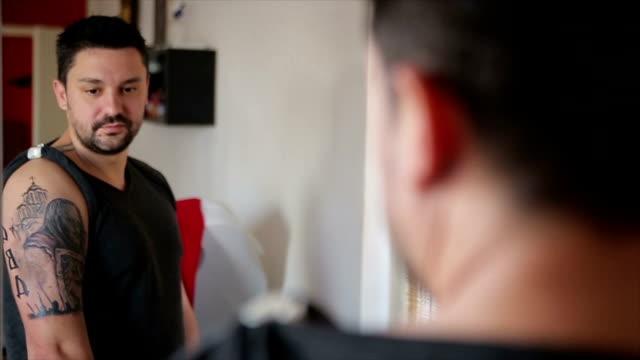 vídeos y material grabado en eventos de stock de los hombres se ve en el espejo su nuevo tatuaje arte en el hombro - mostrar