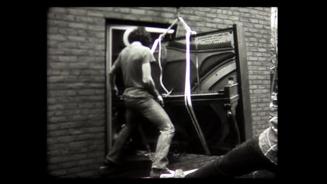 1973 men lower piano out window with pulleys - position stock-videos und b-roll-filmmaterial