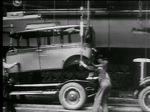 B/W 1927 men lowering body of car onto chassis on assembly line in factory / New York State