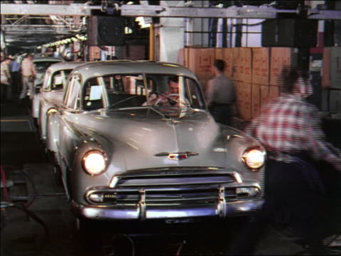 vídeos y material grabado en eventos de stock de 1951 men lowering hood + driving newly built car off assembly line / chevrolet - 1951