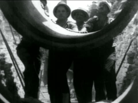 b/w 1934 men lowering piece of concrete pipe in wpa sewage construction project / documentary - new deal video stock e b–roll