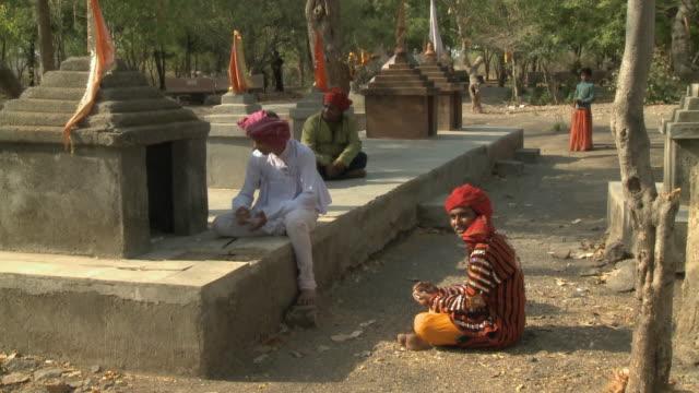 ws men making offering at shrine / rajkot, india - auf dem boden sitzen stock-videos und b-roll-filmmaterial