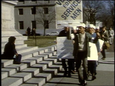 men marching in front of federal building, carrying signs, during vietnam protest / washington, d.c., united states - war veteran stock videos & royalty-free footage