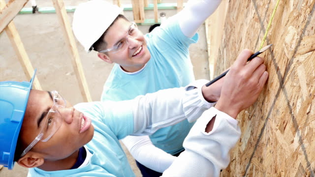Men measure and mark plywood for house being built for charity